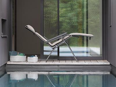 Fauteuil de relaxation LAFUMA Mobilier en position zéro gravité situé au bord d'une piscine