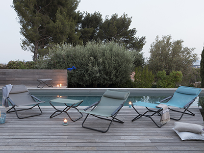LAFUMA Mobilier sun loungers and footrests set up around a pool