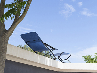 LAFUMA Mobilier sun lounger in Outremer colourway shown on a rooftop terrace