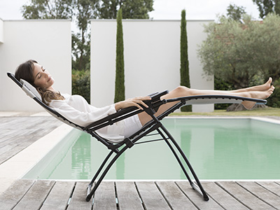 Relaxing on a relax chair in a zero gravity position next to a pool